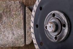 Il taglio di pietra con un disco del diamante ha montato in una smerigliatrice Lavoro in un'officina di pietra immagini stock libere da diritti