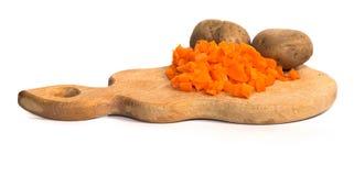 Il taglio ha bollito le carote e la patata in una buccia su un bordo di legno Fotografia Stock