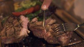Il taglio manuale maschio ha grigliato la bistecca della carne con il coltello e la forcella mentre cena in ristorante con barbec video d archivio