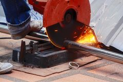 Il taglio maschio di uso del lavoratore ha visto a tagliare una metropolitana spessa dell'acciaio inossidabile immagine stock