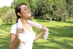 Il tatto sportivo della donna si rilassa nell'ambito del sole al parco con ai fresco Immagini Stock Libere da Diritti