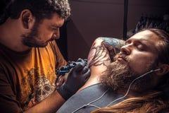 Il tatuatore professionale fa il tatuaggio fresco nel salone del tatuaggio Immagini Stock
