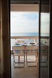Il tavolo da pranzo ha messo su un balcone che trascura il mare Fotografia Stock