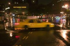 Il taxi giallo d'accelerazione guida giù la strada bagnata piovosa di New York alla notte con le luci, New York Fotografia Stock