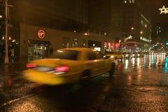 Il taxi giallo d'accelerazione guida giù la strada bagnata piovosa di New York alla notte con le luci, New York Immagine Stock