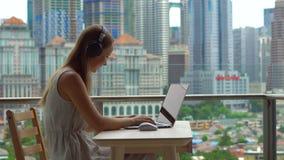 Il techer a distanza ha una conversazione con uno studente attraverso Internet ad un balcone con un fondo di un centro urbano video d archivio