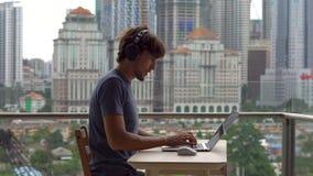 Il techer a distanza ha una conversazione con uno studente attraverso Internet ad un balcone con un fondo di un centro urbano stock footage