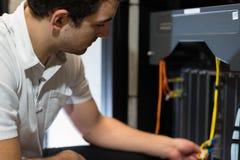 IL technicien avec l'équipement du réseau et l'ordinateur portable Photo libre de droits