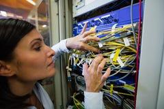 Il tecnico che controlla i cavi in uno scaffale ha montato il server Immagini Stock