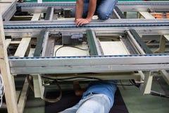 Il tecnico che ripara nastro trasportatore in fabbrica Immagine Stock