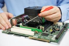 Il tecnico del computer sta controllando la scheda madre del computer fotografie stock