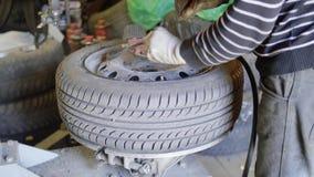 Il tecnico dell'automobile dell'uomo finisce di pompare la gomma sulla ruota nel garage di servizio di riparazione automatica archivi video