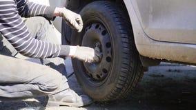 Il tecnico dell'automobile dell'uomo sostituisce la gomma della ruota di automobile sulla strada in via il giorno soleggiato archivi video