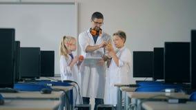 Il tecnico di laboratorio maschio e due bambini stanno stando in un centro di calcolo e stanno osservando i dettagli di riserva archivi video