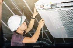 Il tecnico esegue il refrigerante del condizionamento d'aria dal carro armato immagini stock libere da diritti