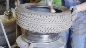 Il tecnico maschio dell'automobile usa la spazzola per lubrificare la gomma sulla ruota nel garage automatico di servizio stock footage