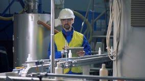 Il tecnico maschio sta osservando le bottiglie di plastica muoversi lungo la cinghia video d archivio