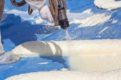 Il tecnico si è vestito in una schiuma di spruzzatura uniforme i di bianco protettivo fotografie stock