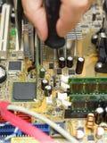 Il tecnico sta riparando il computer facendo uso del cacciavite fotografie stock