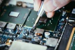 Il tecnico sta riparando un circuito, una mano e un cacciavite del computer fotografia stock