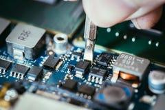 Il tecnico sta riparando un circuito, una mano e un cacciavite del computer fotografia stock libera da diritti