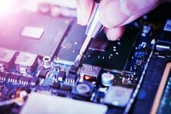 Il tecnico sta riparando un circuito, una mano e un cacciavite del computer immagini stock