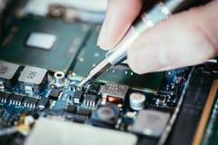 Il tecnico sta riparando un circuito, una mano e un cacciavite del computer fotografie stock libere da diritti