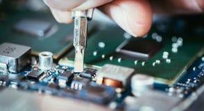 Il tecnico sta riparando un circuito, una mano e un cacciavite del computer immagini stock libere da diritti