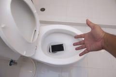Il telefono è caduto nell'arco della toilette Fotografia Stock