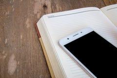Il telefono è disposto su un taccuino su un vecchio bastone di legno Immagine Stock