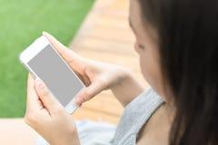 Il telefono cellulare asiatico della tenuta della mano della donna e la copia in bianco spaziano il ghiaione Fotografie Stock