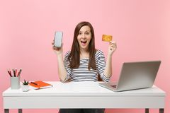 Il telefono cellulare colpito della tenuta della donna con lo schermo vuoto in bianco, carta di credito si siede il lavoro allo s immagini stock