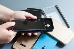 Il telefono cellulare di plastica riveste la varietà su gray Immagine Stock