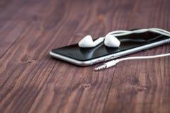 Il telefono cellulare e le cuffie mettono su una vecchia tavola di legno Fotografia Stock