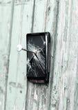 Il telefono cellulare obsoleto è inchiodato ad un recinto di legno immagine stock