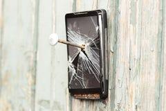 Il telefono cellulare obsoleto è inchiodato ad un recinto di legno fotografia stock libera da diritti