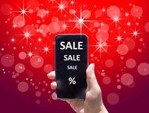 Il telefono con la VENDITA del testo in mano femminile sui precedenti rossi Fotografia Stock