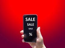 Il telefono con la VENDITA del testo in mano femminile sui precedenti rossi Immagine Stock Libera da Diritti