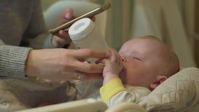 Il telefono della madre alimenta il bambino video d archivio