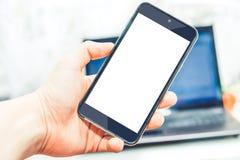 Il telefono ha tenuto in mani nel computer portatile del fondo Immagine Stock