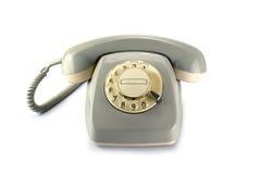 Il telefono rotatorio d'annata, gray ha ingiallito la plastica su un backgrou bianco Fotografie Stock Libere da Diritti