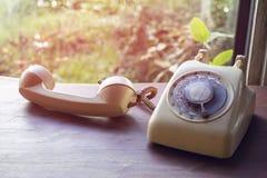 Il telefono vecchio su una tavola di legno con un fondo leggero di tramonto fotografie stock