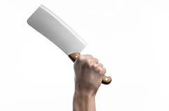 Il tema della cucina: Mano del cuoco unico che giudica un grande coltello da cucina per il taglio della carne su un fondo bianco  Immagini Stock Libere da Diritti