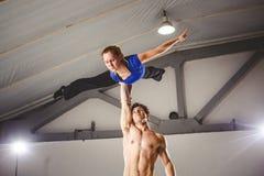Il tema di Acroyoga e delle pose di yoga Pratica di Acroyogis con la lampadina dello studio le tenute della base dell'uomo nell'e Fotografia Stock