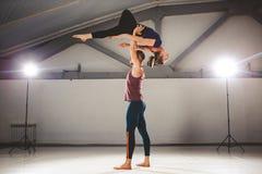 Il tema di Acroyoga e delle pose di yoga Una coppia due uomini e una donna sta nella posizione del asana Il tipo giudica Immagine Stock Libera da Diritti