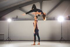 Il tema di Acroyoga e delle pose di yoga Una coppia due uomini e una donna sta nella posizione del asana Il tipo giudica la ragaz Fotografia Stock