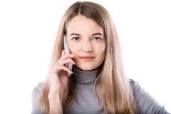Il tema di una donna di affari e delle conversazioni telefoniche La bella giovane donna caucasica utilizza un microtelefono dello immagini stock