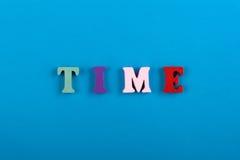 Il tempo è alto corrente Cronometri la parola composta dalle lettere di legno variopinte su fondo blu Immagine Stock Libera da Diritti