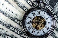 Il tempo è denaro con l'orologio da tasca d'annata sulle banconote u del dollaro americano Fotografia Stock Libera da Diritti
