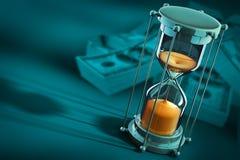 Il tempo è denaro concetto con l'orologio ed i dollari della sabbia Fotografia Stock